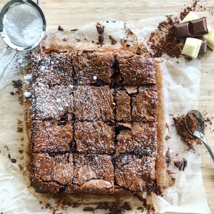 Chocolate brownies, sieve and chocolate on chopping board