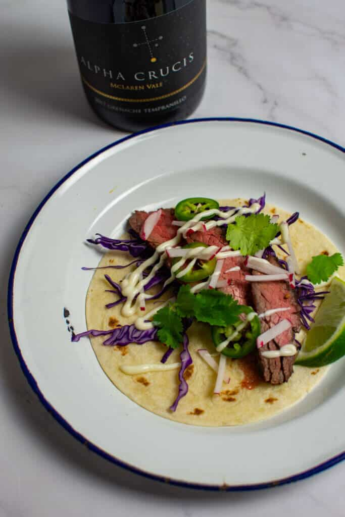steak taco carne asada style on a plate with a chalk hill alpha crucis grenache wine in backgroundte