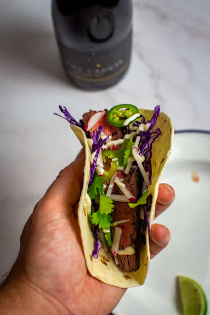 someone holding a steak taco carne asada style with a chalk hill alpha crucis grenache wine in backgrounde with a chalk hill alpha crucis grenache wine in background