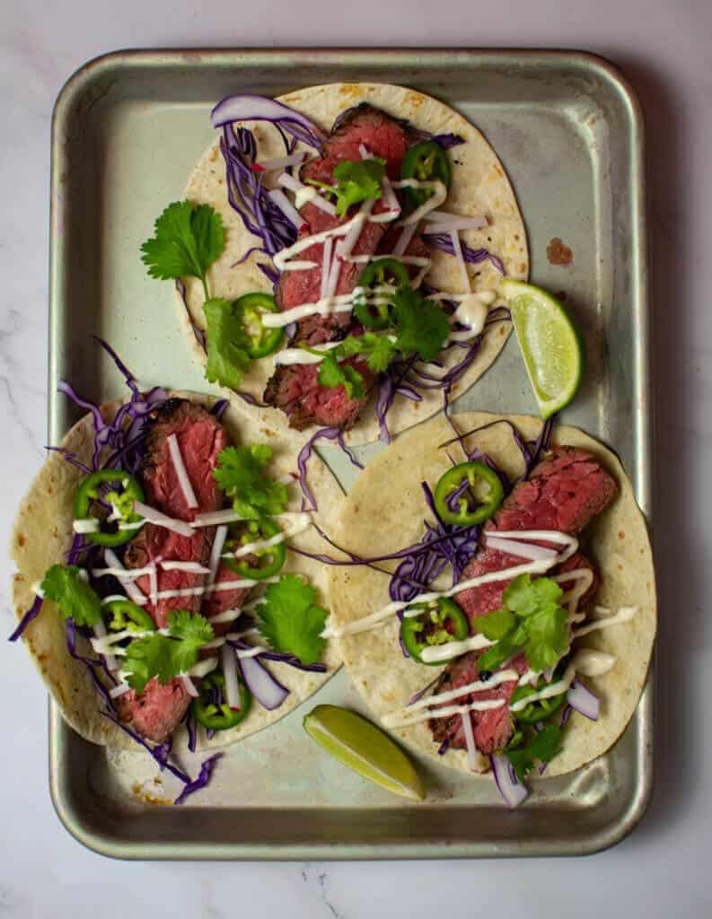 3 steak tacos - carne asada style on a tray