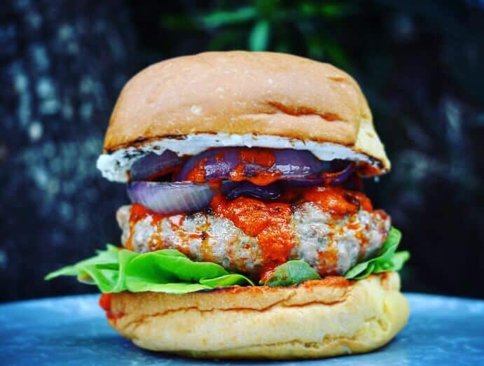Lamb burger with harissa, red onion and lettuce on a plate