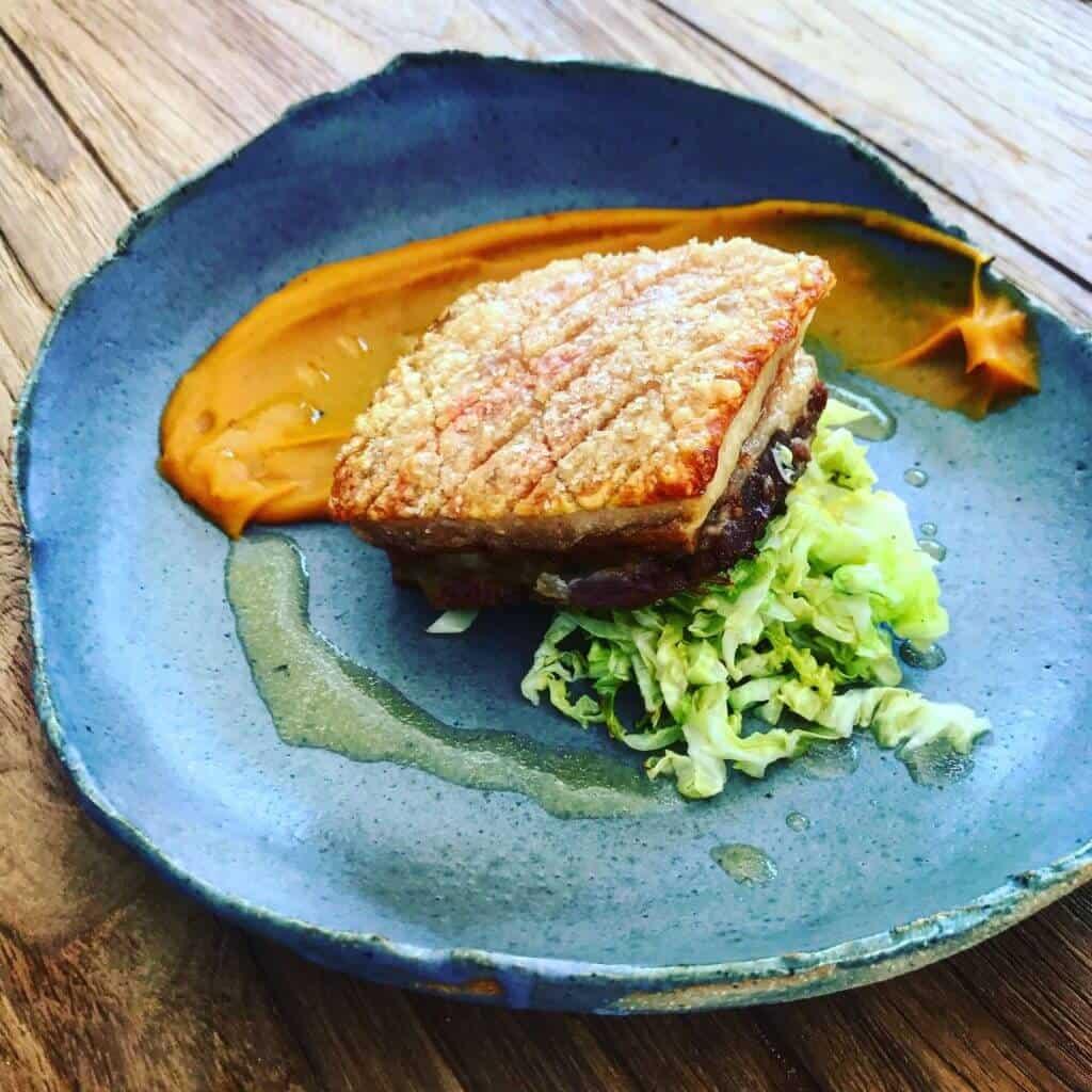 Crispy pork belly, sweet potato puree, cabbage & cider sauce on a plate