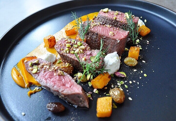lamb loin on a plate with vegetables and pistachio dukkah