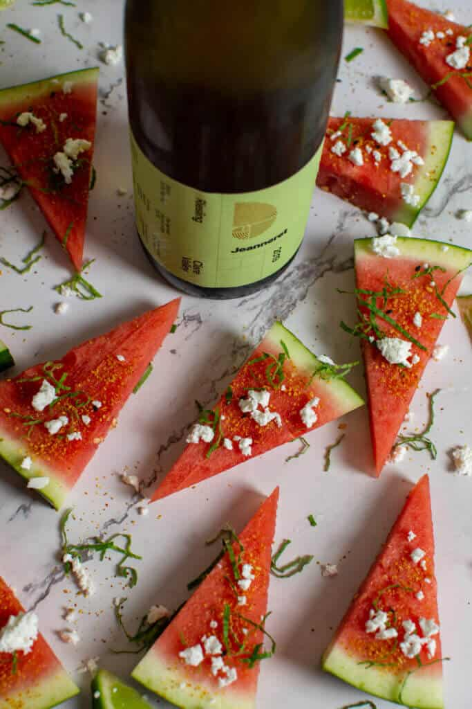 watermelon topped with togaroshi, mint & feta. Bottle of Jeanneret riesling next to them