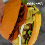 someone holding an organic beef burger with brie, roasted tomatoes & onion marmalade