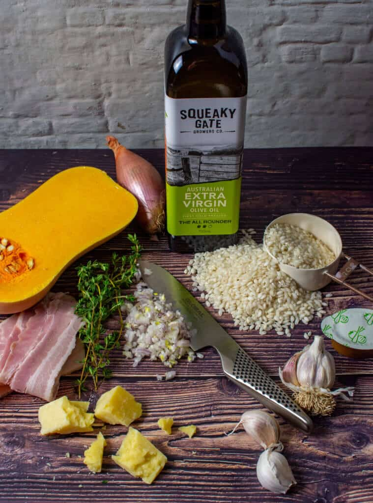squeaky gate olive oil, pumpkin, bacon, risotto rice & a global chef knife on a table