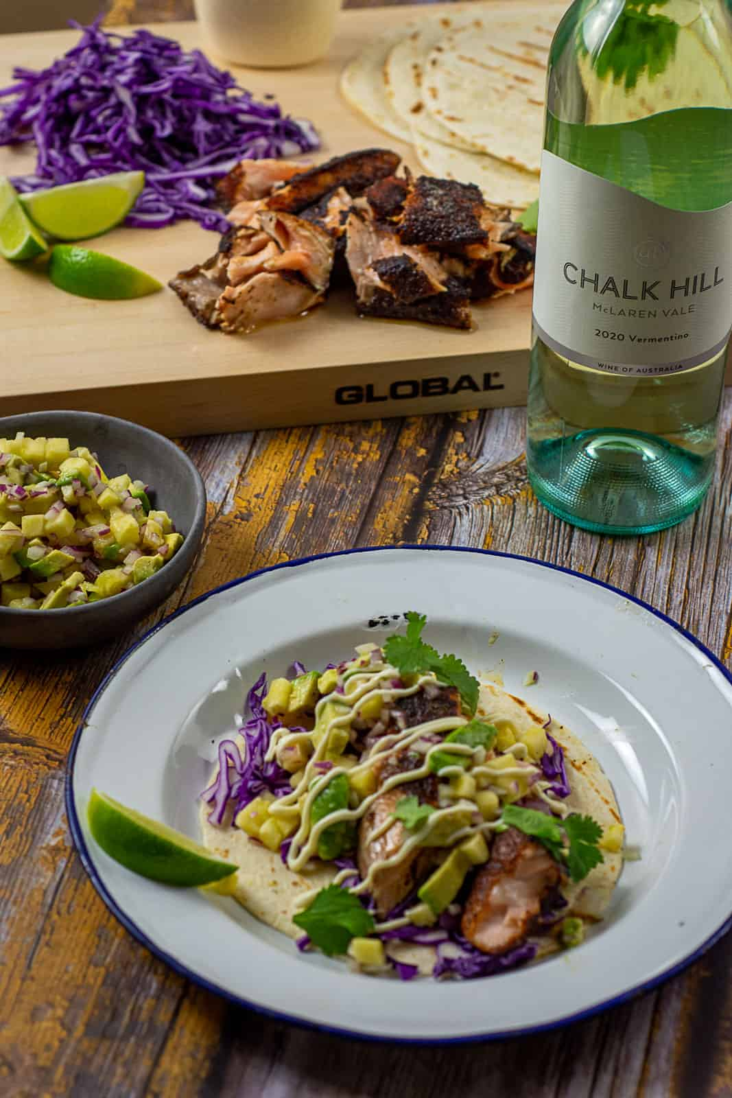 blackened salmon taco on a plate with chalk hill vermentino in background
