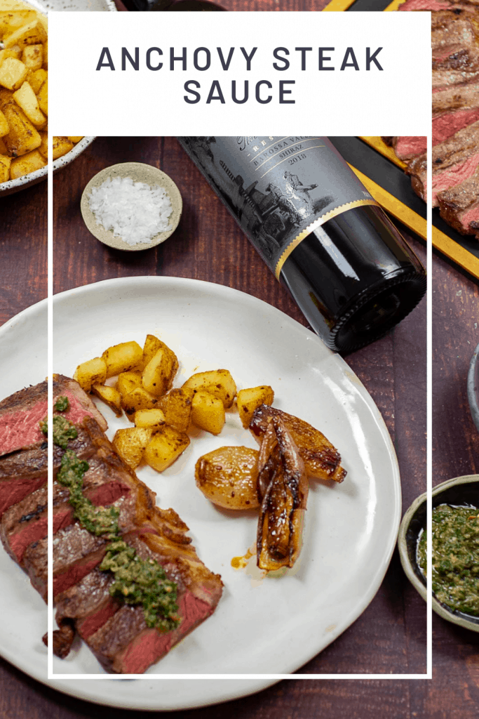 Cooked steak topped with anchovy steak sauce & potatoes on a plate. Barossa shiraz beside it