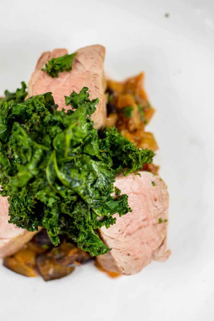 Pork tenderloin, spiced eggplant & crispy kale on white plate