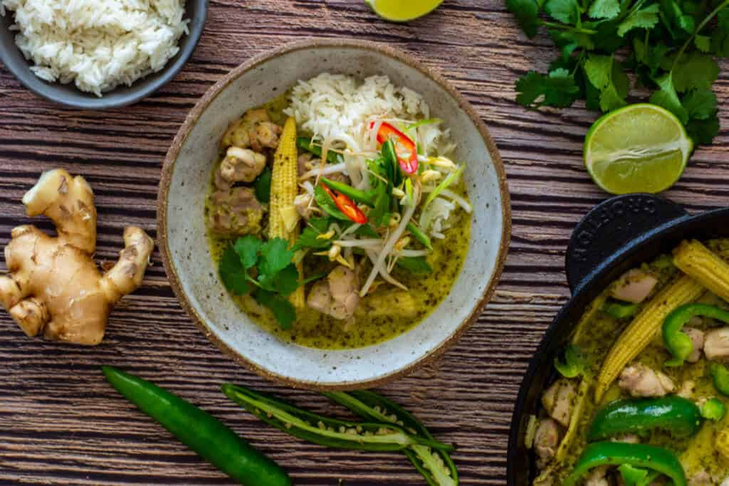 thai green curry in a bowl, coriander, ginger & rice on table