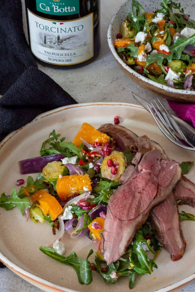 grilled lamb salad, a bowl of roasted veg salad and a bottle of red wine