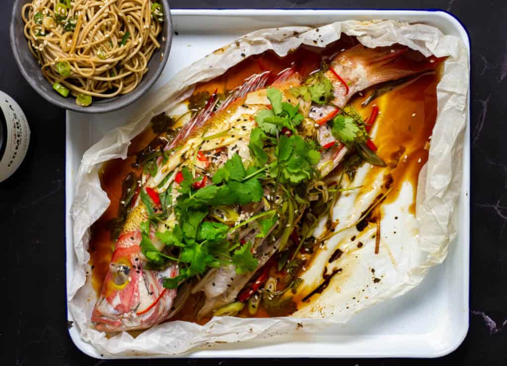 Cooked fish en papillote with bowl of noodles