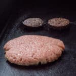 Pork burger and black pudding cooking on a flat top