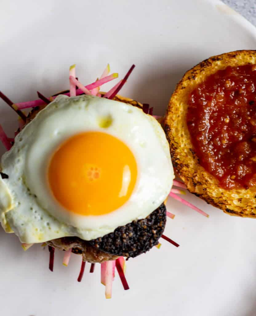 Birds eye view of pork & black burger with a sunny side up egg