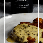 steak, peppercorn sauce on a plate with manser red