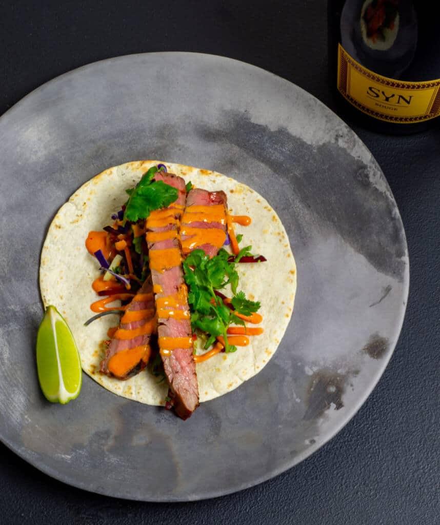 1 korean steak taco on a plate w/ bottle of sparkling shiraz