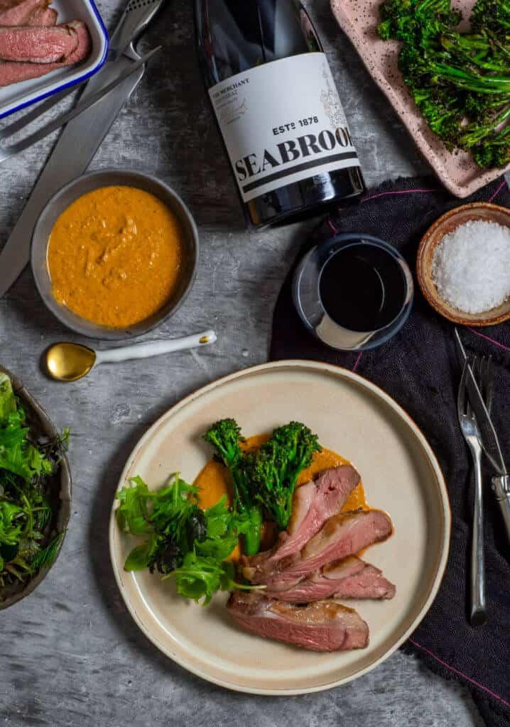 Seabrook wine shiraz, BBQ lamb, romesco sauce & charred broccolini on a table
