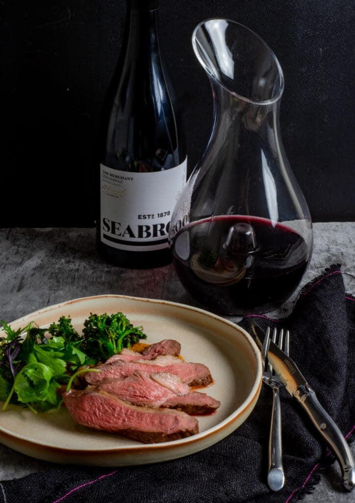 Seabrook wine shiraz, wine decanter, BBQ lamb, romesco sauce & charred broccolini on a table