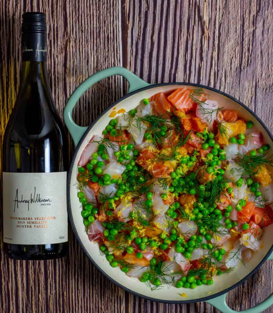 Raw fish, peas & dill in a pan for fish pie and a bottle of wine