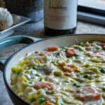 fish pie in pan with wine in background