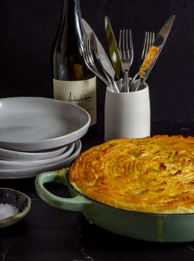 fish pie, wine bottle, plates and cutlery