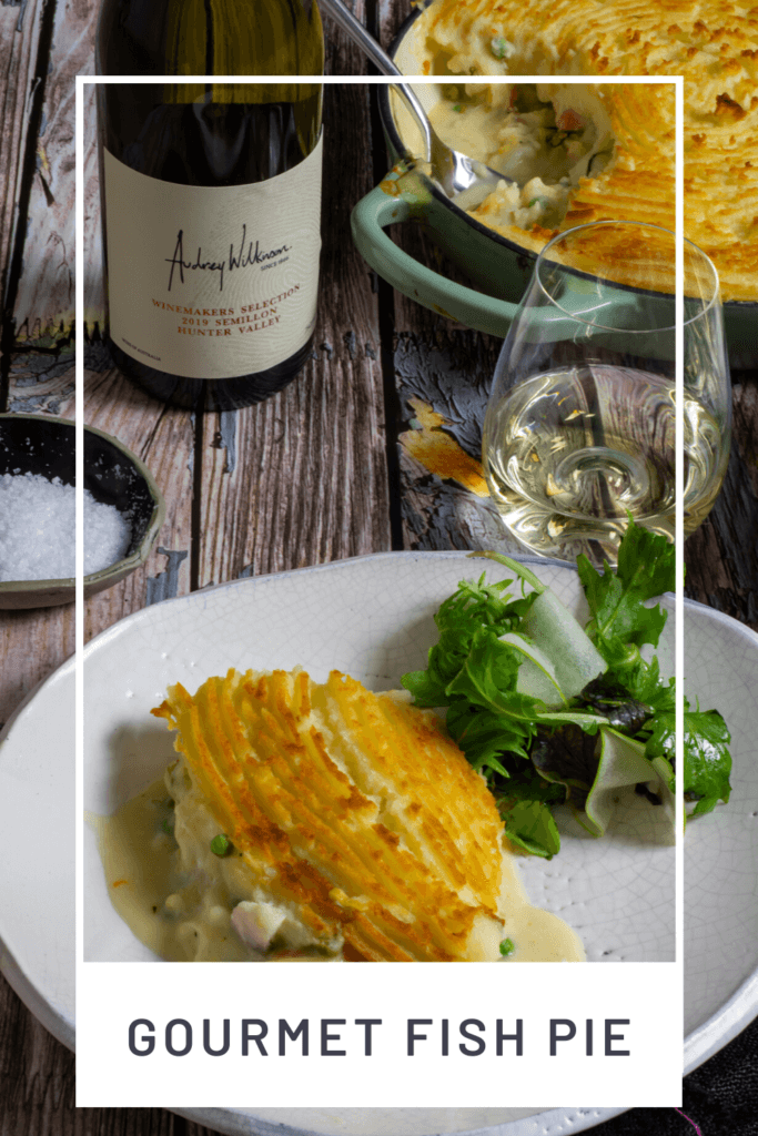 fish pie, glass of wine, wine bottle and salad