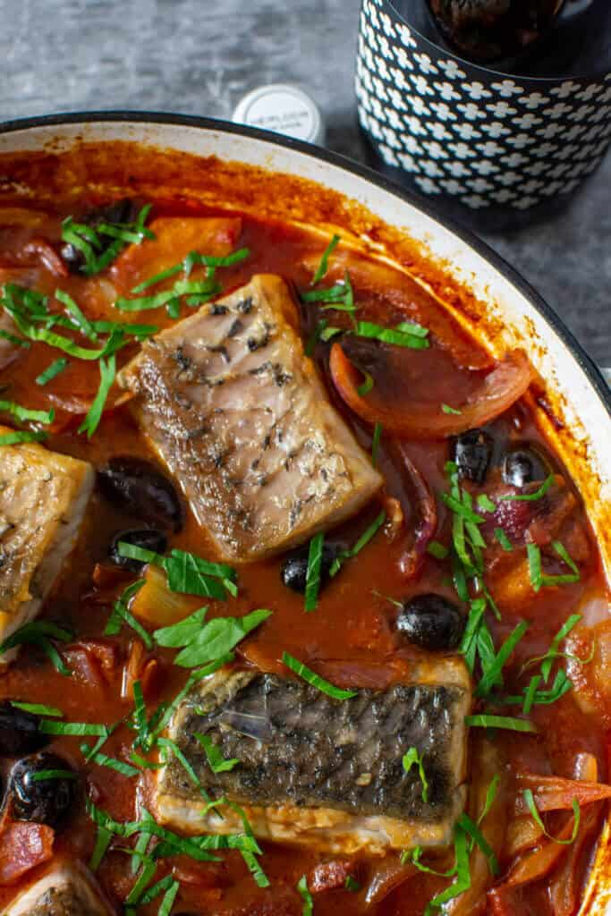 spanish fish stew in a white casserole dish and a bottle of heirloom wine