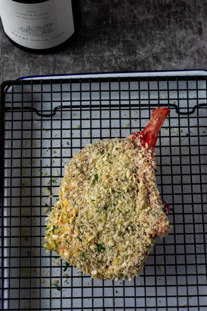 raw crumbed veal cutlet on wire rack on tray
