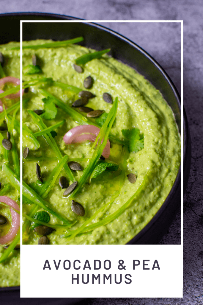 black bowl with avocado & pea hummus topped with pickled onions, pepitas, herbs & snowpeas