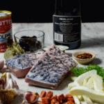 bottle of heirloom wine, barramundi, chorizo & vegetables on counter top