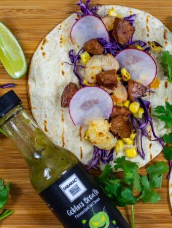 chorizo & prawn tacos on chopping board with sabarac hot sauce