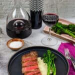 steak & onion soubise on a plate, decanter, glass of wine and bottle heirloom shiraz