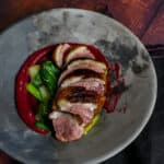 Duck breast, rhubarb ketchup & asian greens in a made of australia bowl on a table