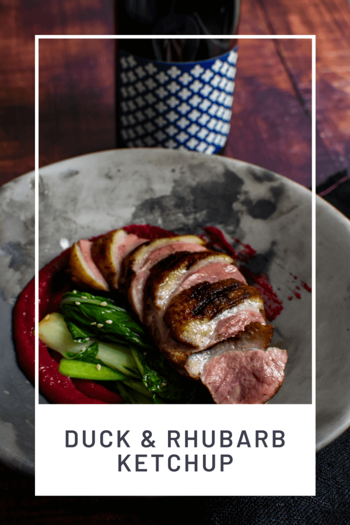 Duck breast, rhubarb ketchup & asian greens in a made of australia bowl on a table with heirloom pinot noir