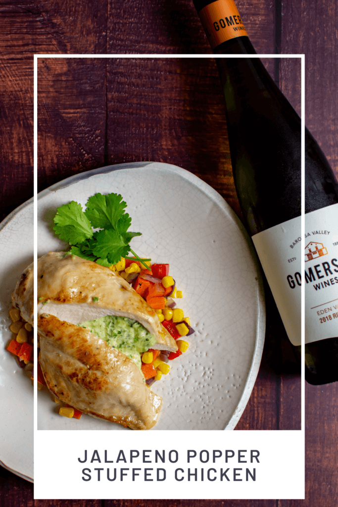 jalapeno popper stuffed chicken on white plate with corn hash and a bottle of gomersal wine