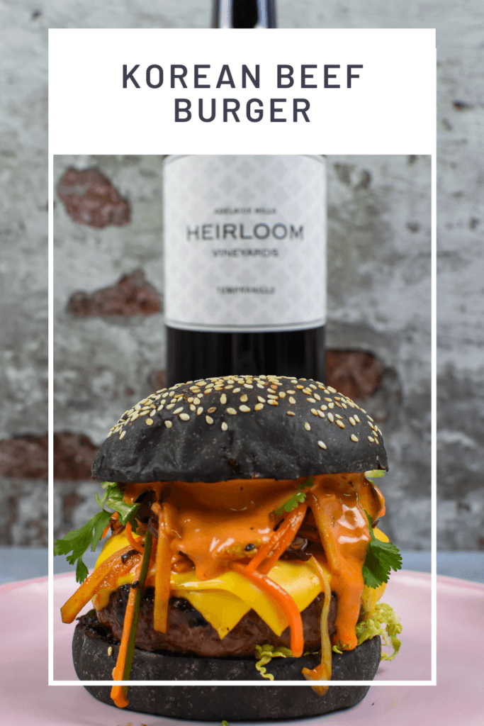 korean beef burger on a pink plate, heirloom tempranillo red wine behind it