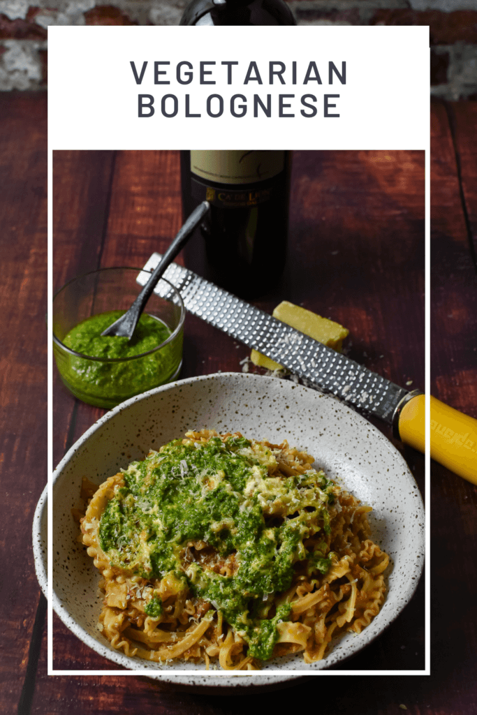 vegetable bolognese with basil pesto & creme fraiche in a bowl. microplane and parmesan cheese & bottle of red wine on the side