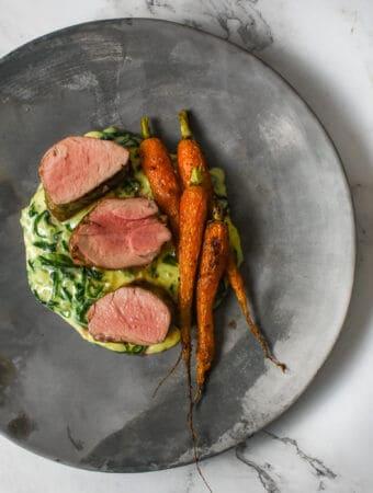 pork tenderloin, creamed spianch & carrots on a made of australia plate