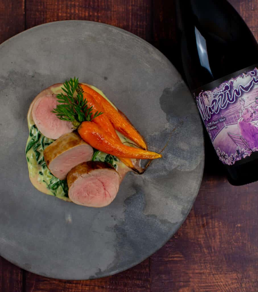 pork tenderloin, creamed spianch & carrots on a made of australia plate with a btl of mazzini pinot noir