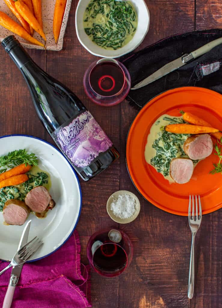 2 plates of pork tenderloin, creamed spinach & carrots, mazzini pinot noir and cutlery on a table