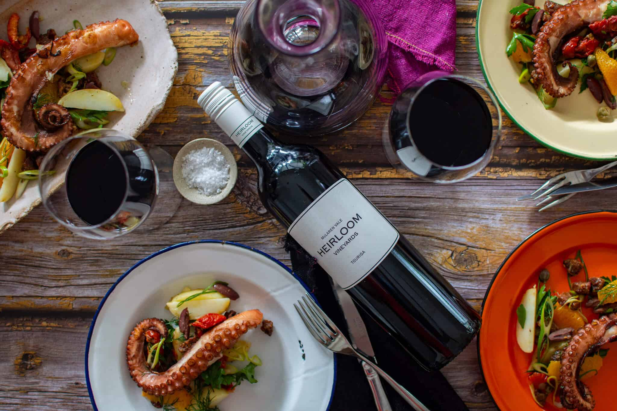 birds eye view of grilled octopus salad, wine glasses, cutlery and bottle of heirloom wine