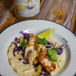 grilled fish taco on a plate with a bottle of marri wood park pet nat behind it