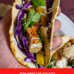 someone holding a grilled fish taco