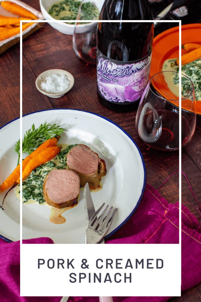 2 plates of pork tenderloin, creamed spinach & carrots, mazzini pinot noir and cutlery on a table