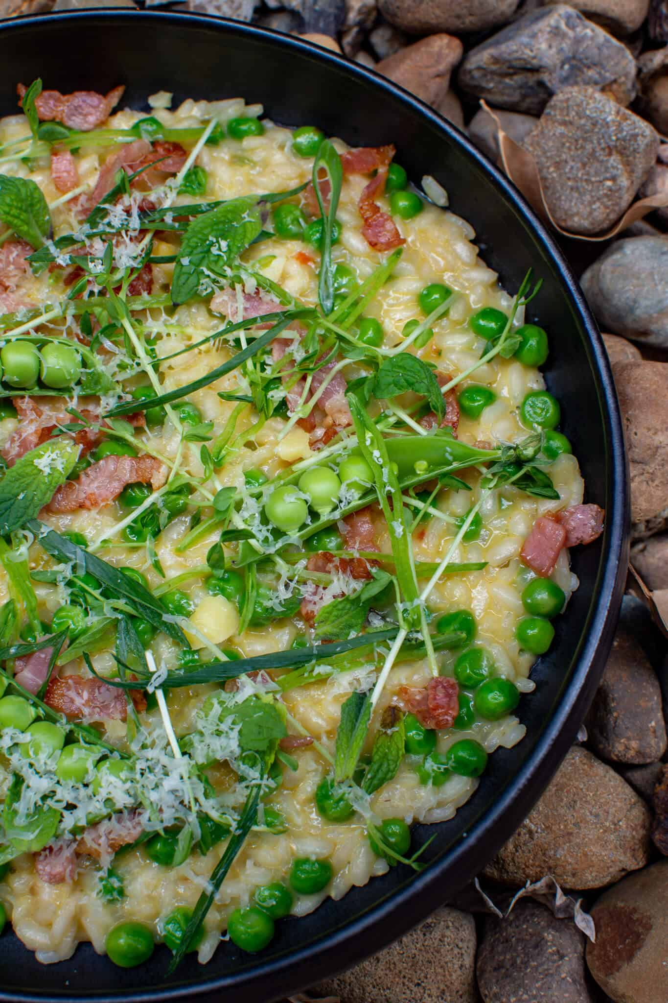 pea & bacon risotto in a black bowl on top of loads of stones