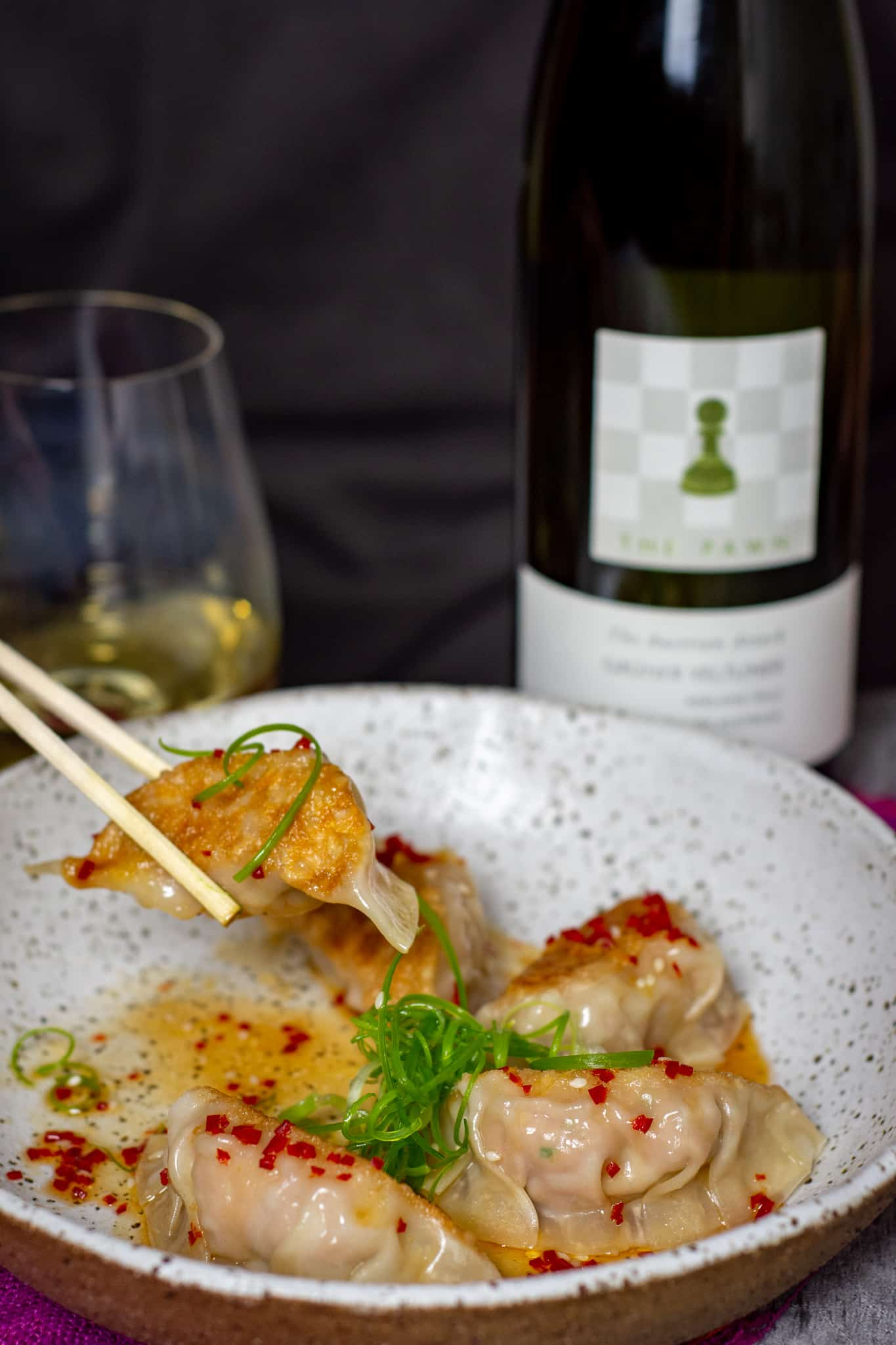 someone eating pork & prawm dumplings with chopsticks and a bottle of The Pawn Wine Co gruner veltliner in background