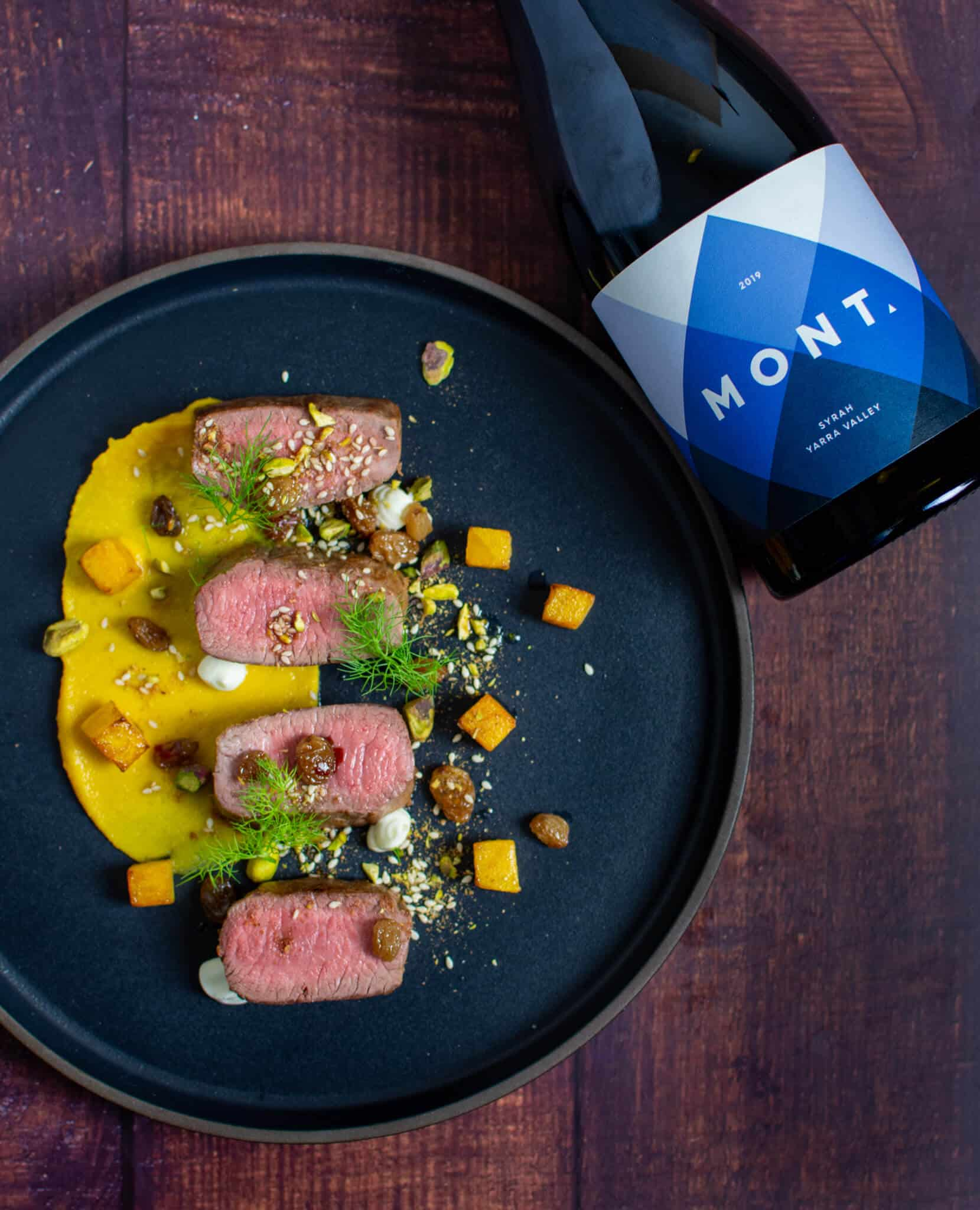 lamb, smoked squash puree, & pistachio dukkah on a black plate with mont wines syrah next to it