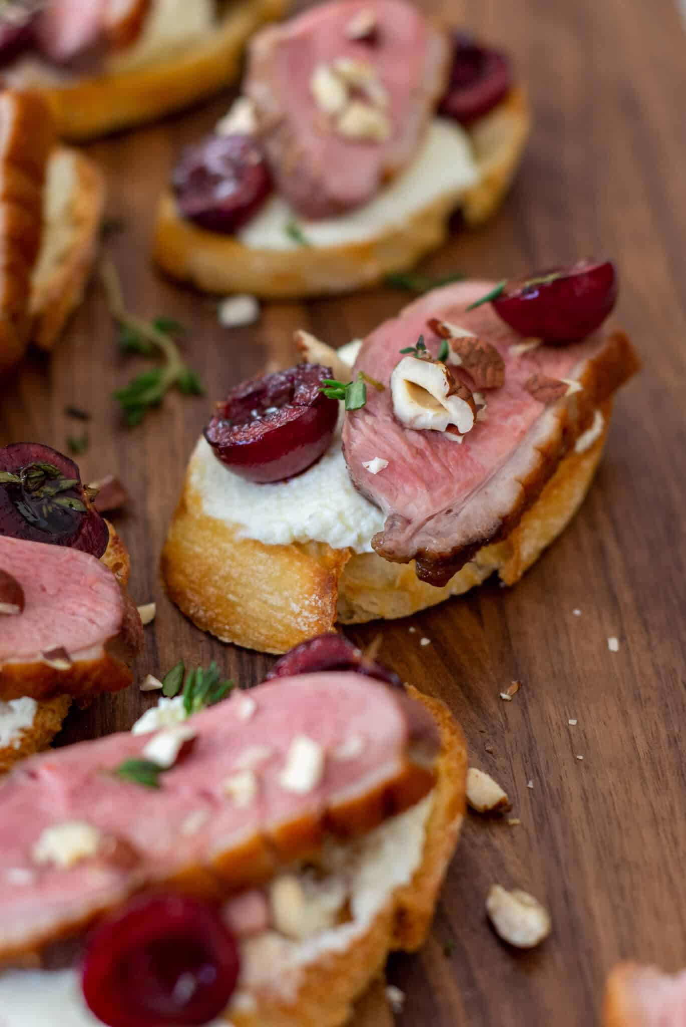 duck crostinis with cherries & goat cheese on wooden chopping board