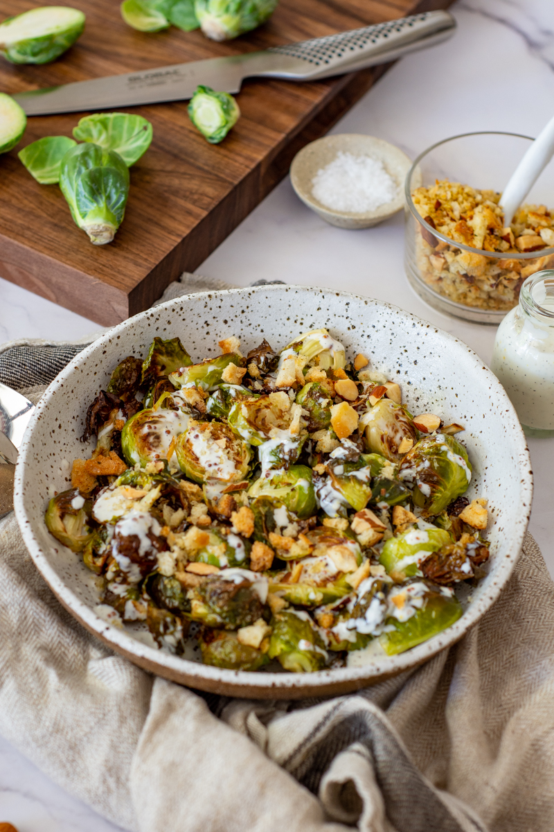 charred brussel sprouts & pangrattato in a bowl with a chopping board, brussel sprouts in the background