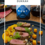 lamb, smoked squash puree, & pistachio dukkah on a black plate with mont wines syrah & wine glasses next to it
